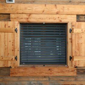 Détail d'une fenêtre comportant volets et stores à lamelles